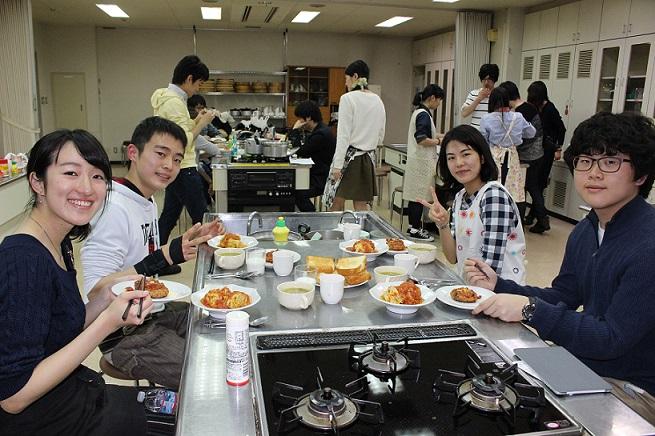 完成した夕食を前に笑顔を見せるメンバー